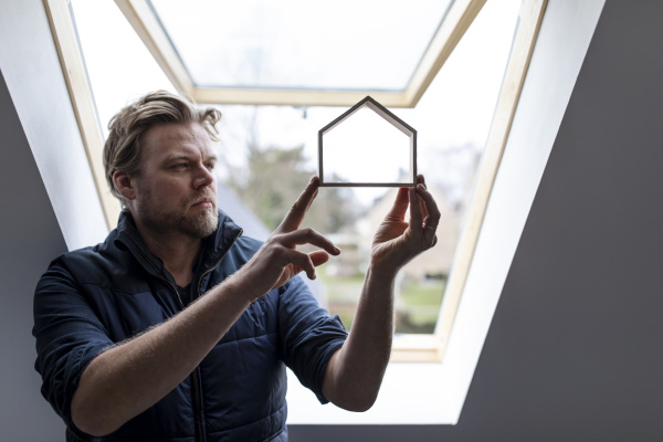 architect looking through wooden house model