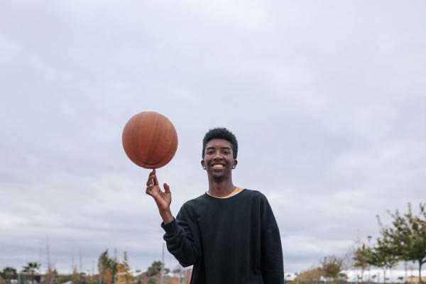 teenager balancing basketball on his finger