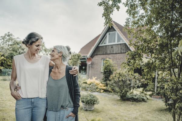 mother and daughter standing in garden