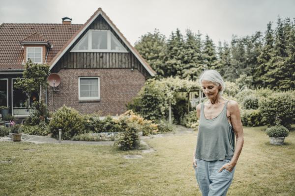 senior woman walking her garden with