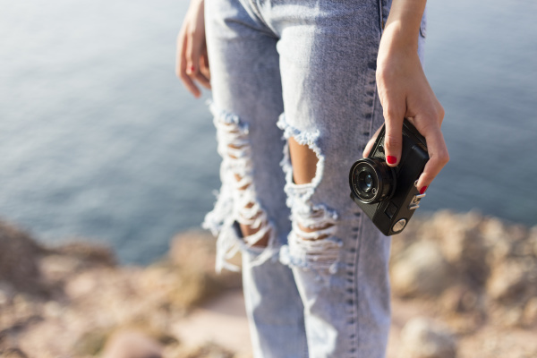 female teenager holding camera outdoors