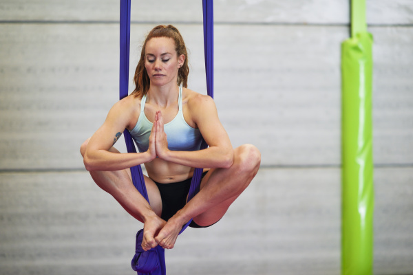young woman doing aerial silk in