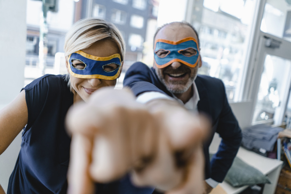 businessman and woman wearing super hero