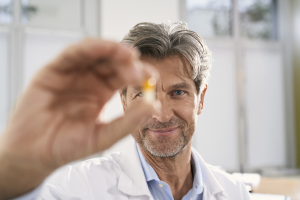 portrait of doctor holding capsule in