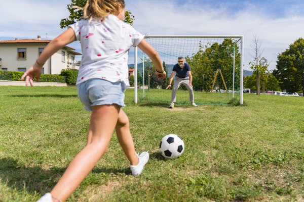 father and daughter playing football on