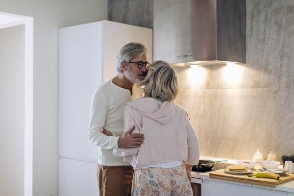 affectionate mature couple in kitchen at