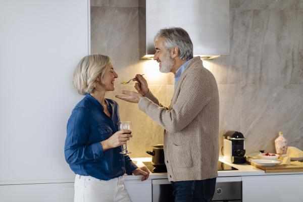 happy mature couple preparing dinner in