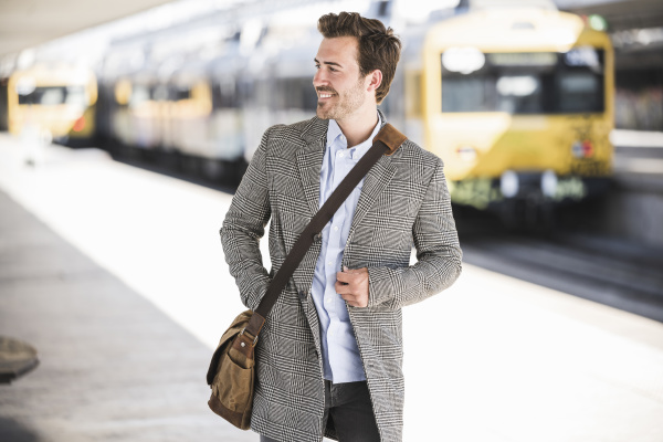 smiling young businessman at the train