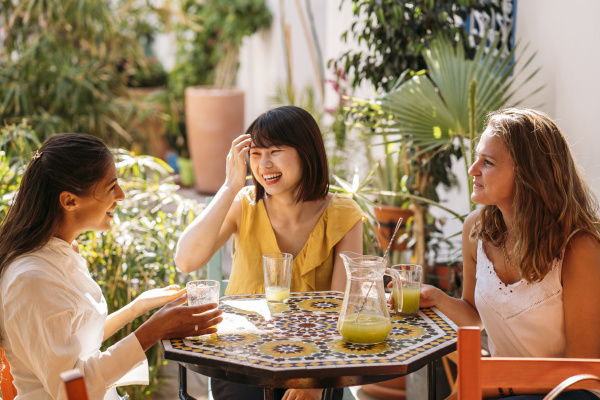 three happy female friends meeting in