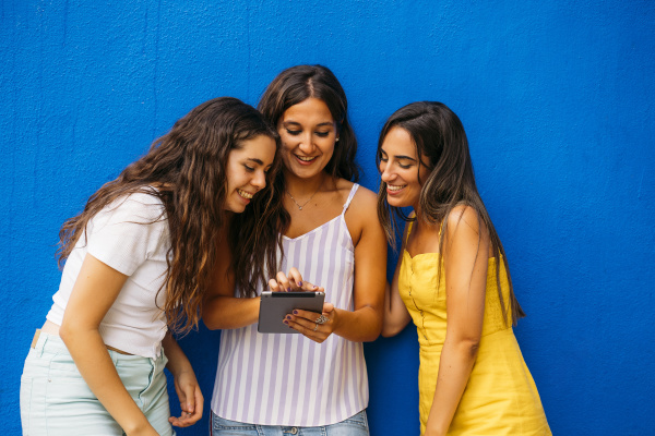 three happy female friends standing at
