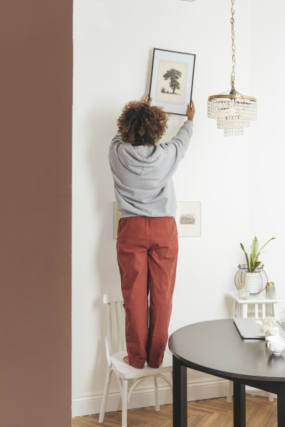 young woman hanging up picture at