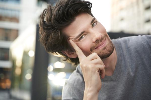 portrait of smiling man wearing grey