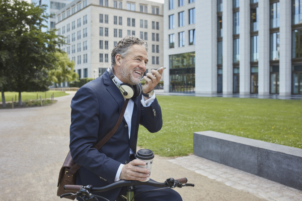 mature businessman with bicycle using smartphone