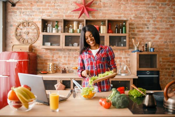 black woman looking recipe on laptop