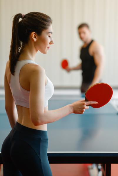 man and woman playing ping pong
