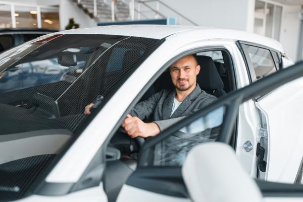man sitting in new car showroom