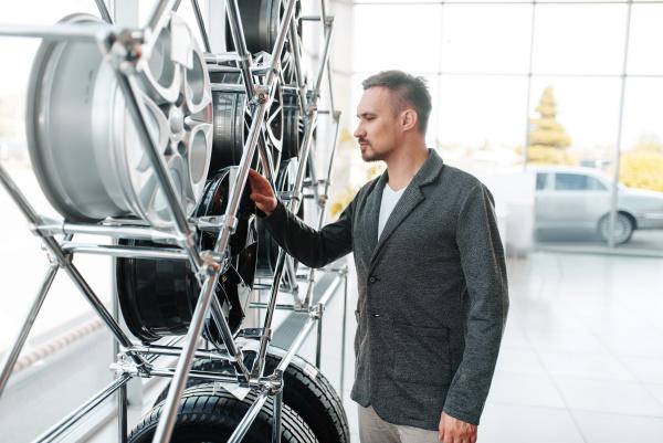 man choosing wheels for new car