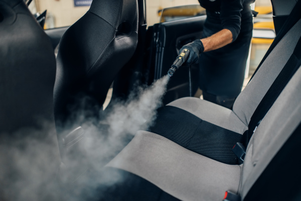 carwash worker cleans seats with steam