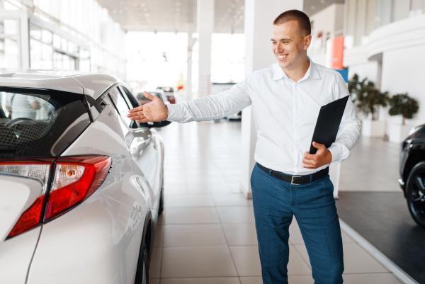 salesman shows new car in showroom