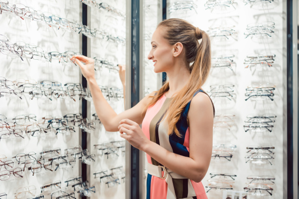 woman choosing new glasses out of