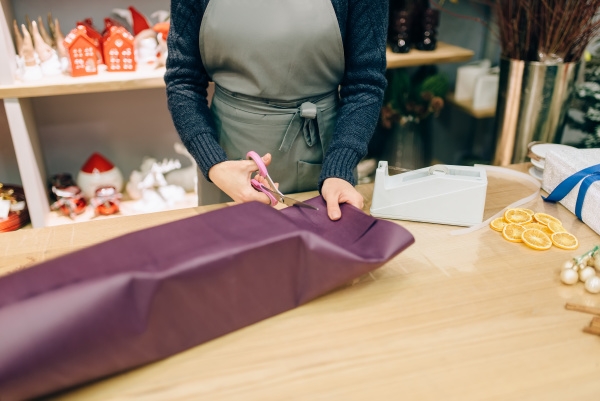 female seller cuts wrapping paper with