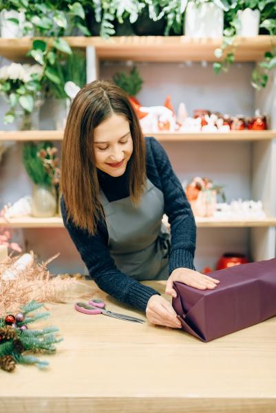 smiling seller packing gift box in