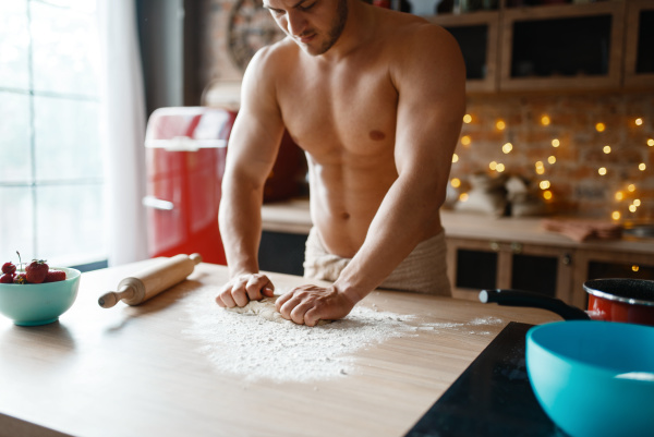 muscular husband in underwear cooking on