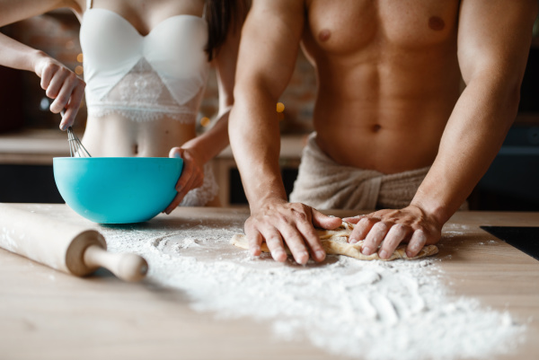 young couple in underwear cooking on