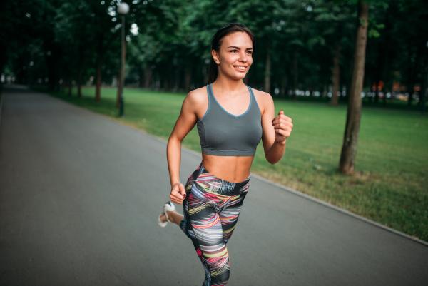 slim woman jogging on sidewalk in