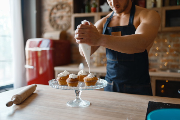 nude man in apron cooking dessert