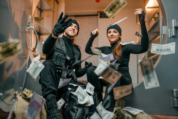 happy robbers throwing money at the