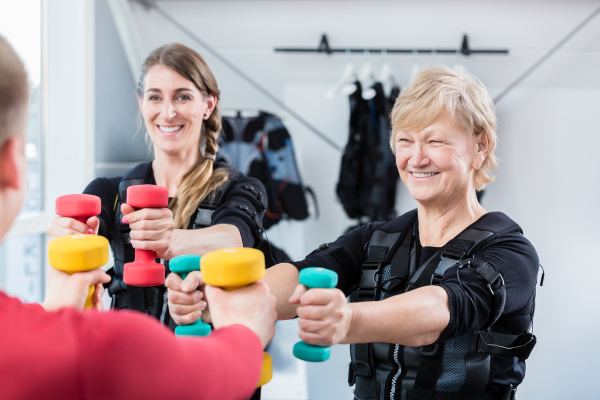 senior and young woman with dumbbells