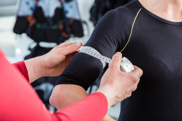 coach measuring biceps muscle of woman