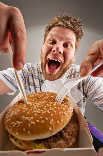 man with knife and fork eating