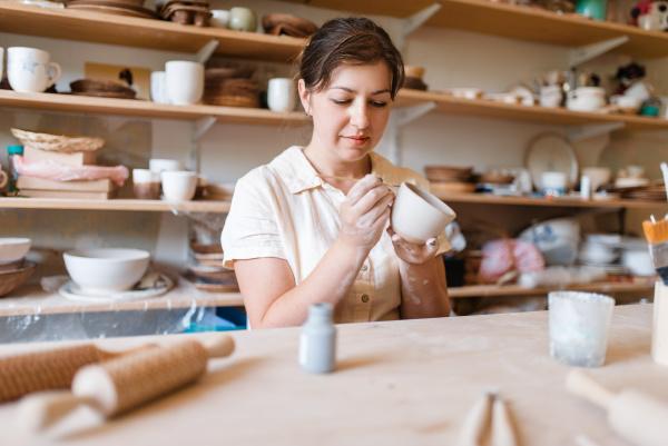 female master paints a pot pottery