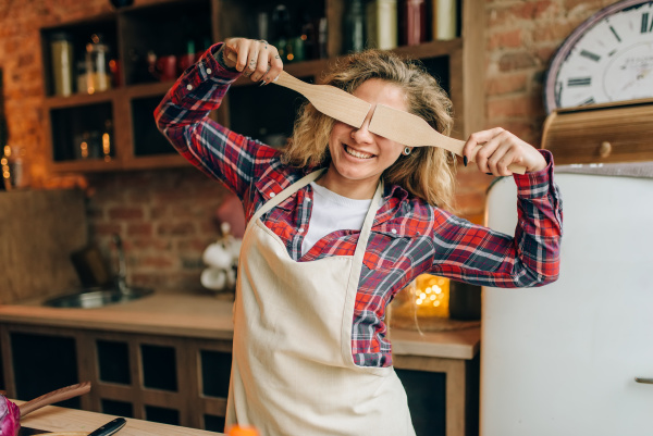 housewife covers her eyes with wooden
