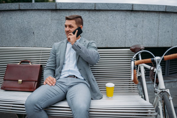 businessman with bike talking by phone
