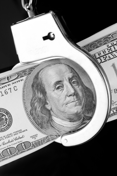 one hundred dollar banknote in handcuffs