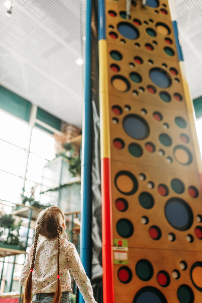 little girl looks on climbing wall