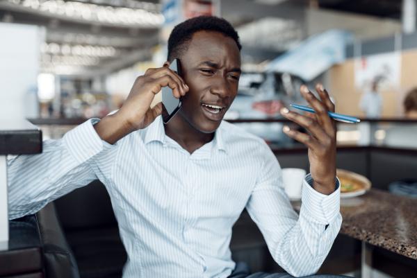 black businessman talking by phone car