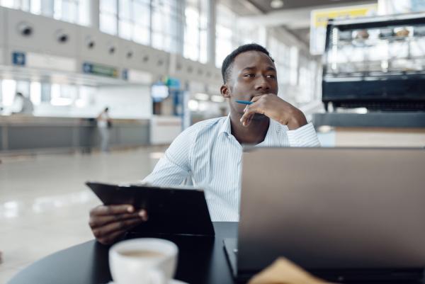 ebony businessman at laptop in car