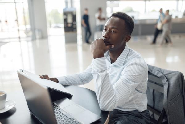 black businessman at laptop in car