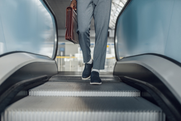 black businessman descending on escalator in