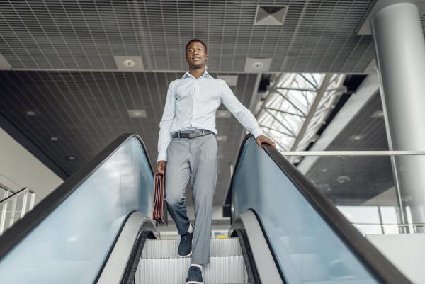 ebony businessman descending on escalator in