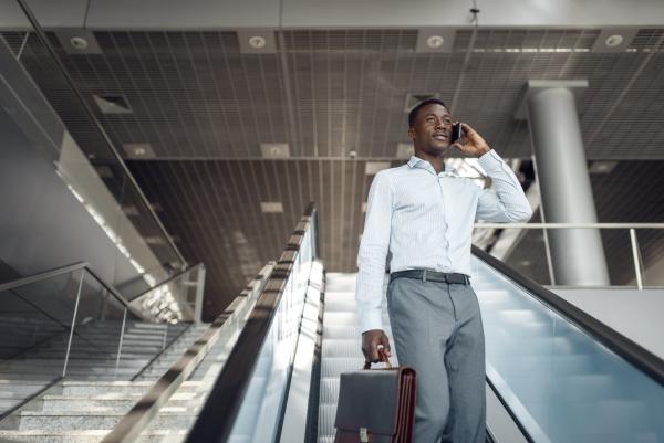 businessman talking by phone on escalator