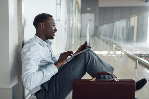 black businessman with laptop sitting on