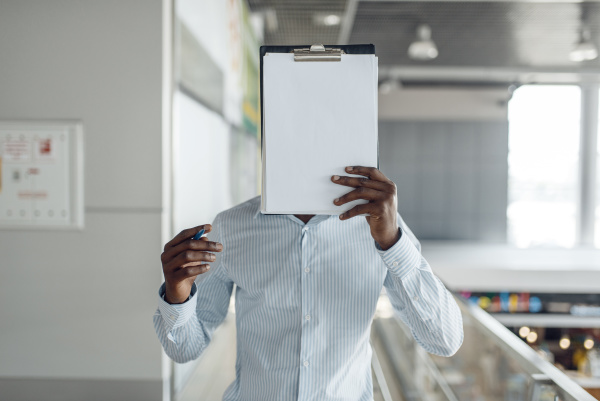 ebony businessman covers his face with