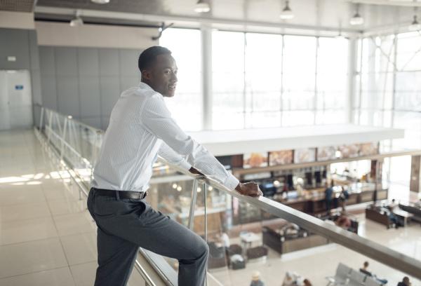 ebony businessman looking on food court
