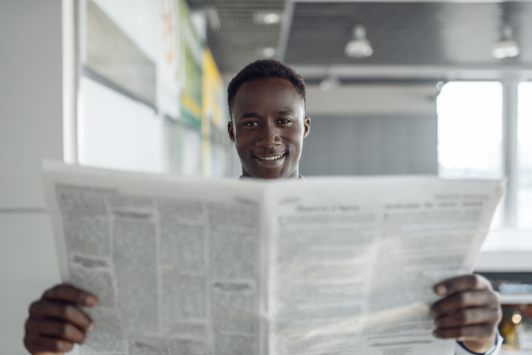ebony businessman with newspaper in office