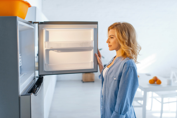young woman opened the fridge on